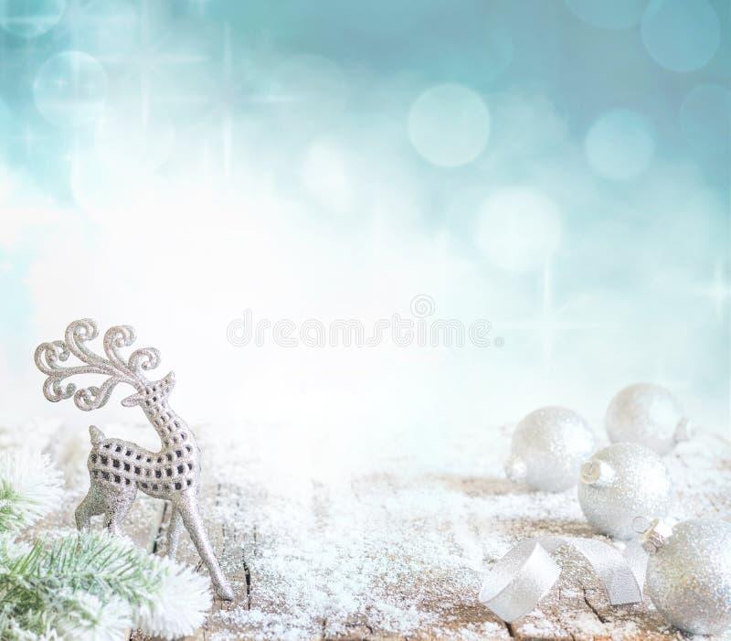 Абстрактная предпосылка рождества с серебряными безделушками и северным оленем на снеге стоковые изображения