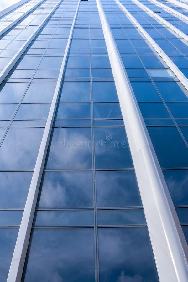 Абстрактная предпосылка фасада современного стеклянного здания с белыми облаками отразила в ей стоковая фотография