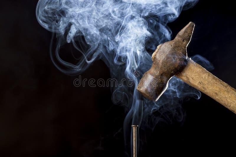 Абстрактное фото молотка металла ржавого над ногтем с дымом на черной предпосылке стоковые изображения rf