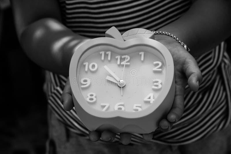 Абстрактное черно-белое изображение изображения милой девушки держа и показывая голубой будильник в ее руке в винтажном стиле стоковые изображения