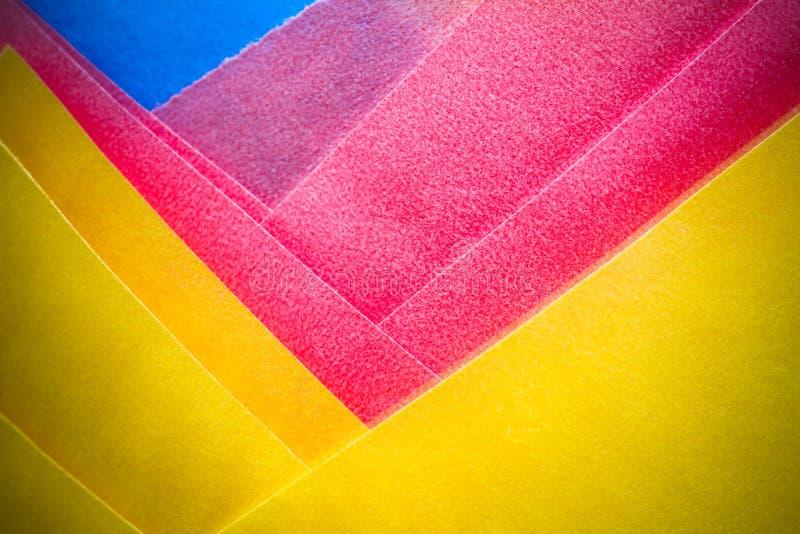 Абстрактные желтый цвет, розовое и синь покрасили бумажное фото макроса слоев как красочная предпосылка текстуры стоковое изображение