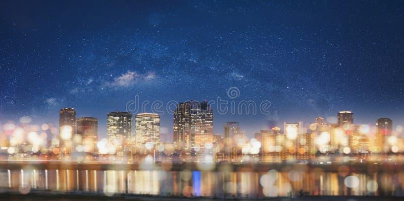 Абстрактный город вечером с предпосылкой света Bokeh Панорамное современное здание вечером с накалять светлое и звездное небо стоковое фото
