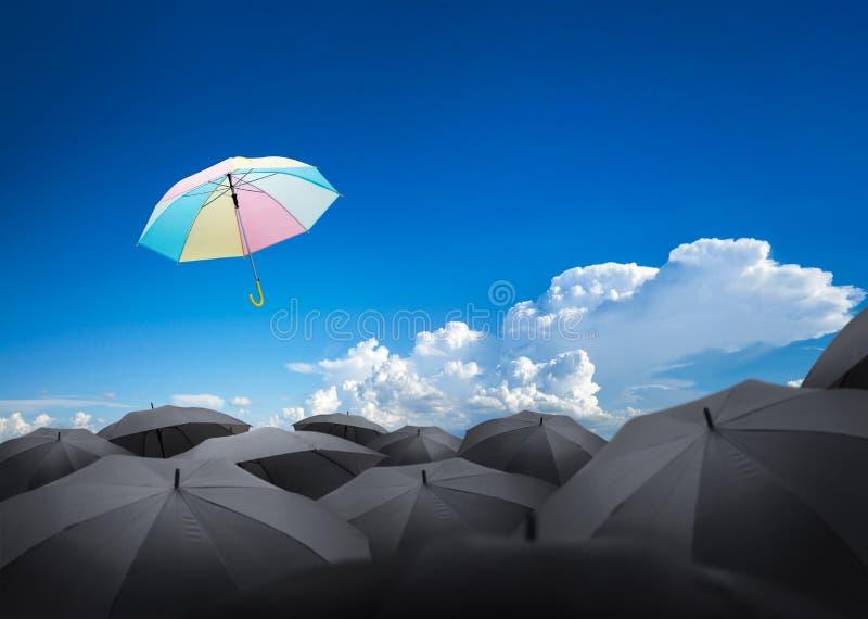 абстрактный зонтик летая над много черных зонтиков с beautifu стоковое изображение rf