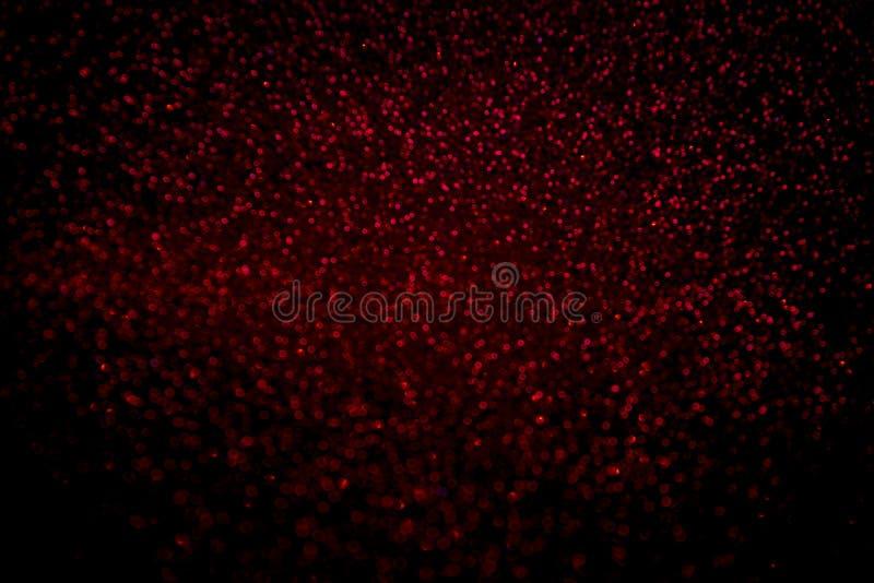 Абстрактный красный confetti яркого блеска сверкнает на черной предпосылке стоковые изображения