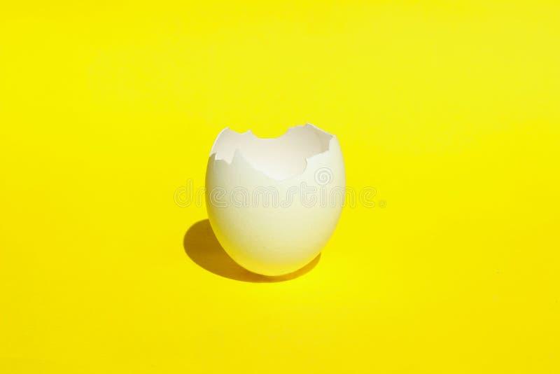 Абстрактный пищевой ингредиент Треснутый конец яйца вверх Сломленный белый Eggshell цыпленка Белый Eggshell над желтой предпосылк стоковые изображения