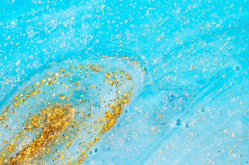 Абстрактный текстурированный шлам предпосылки голубой с золотыми частицами яркого блеска стоковое фото rf