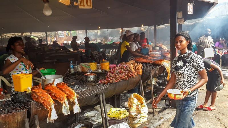АБУДЖА, НИГЕРИЯ, АФРИКА - 3-ЬЕ МАРТА 2014: Неопознанные африканские женщины подготавливая рыб и другой еды на рыбном базаре Абудж стоковые изображения rf