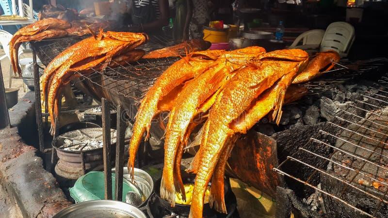 АБУДЖА, НИГЕРИЯ, АФРИКА - 3-ЬЕ МАРТА 2014: Рыбный базар Абуджи с очень вкусными spiced рыбами от угля жарит на предложении стоковое изображение