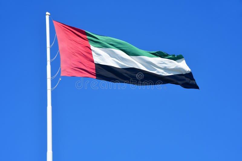 АБУ-ДАБИ, ОАЭ - 19-ОЕ МАРТА 2019: Национальный флаг на предпосылке голубого неба Объениненные Арабские Эмираты стоковая фотография rf