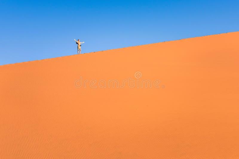 Авантюрный путешественник человека на песчанной дюне в Намибии стоковое фото rf