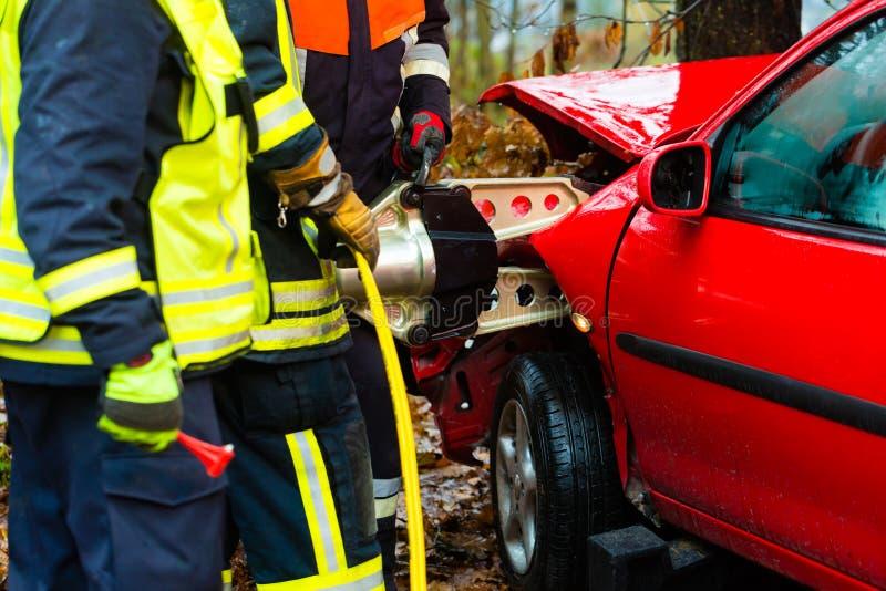 Авария, пожарная команда спашет жертву автомобиля стоковое изображение