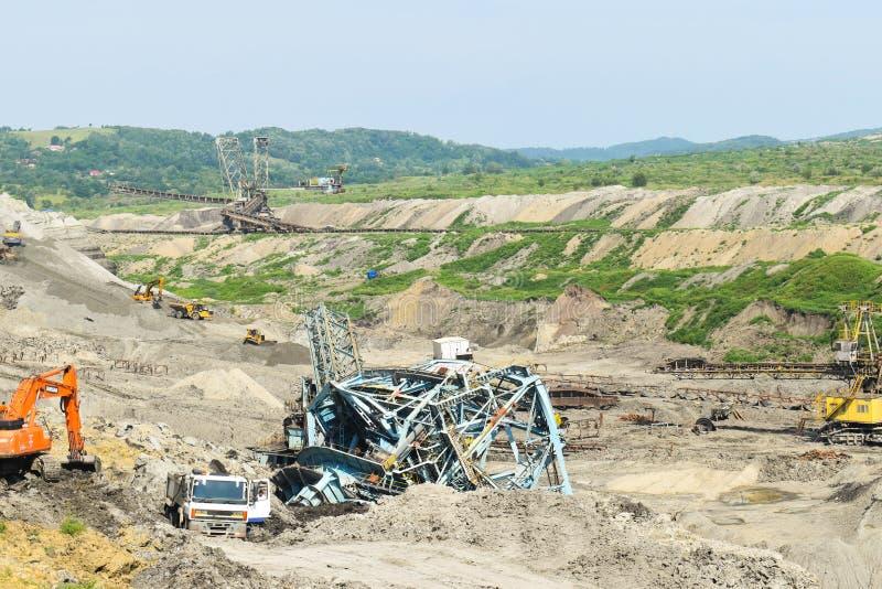Авария угольной шахты с тяжелой машиной извлечения внутри эксплуатирования угля Огромный экскаватор обрушился в открытом карьере стоковая фотография rf