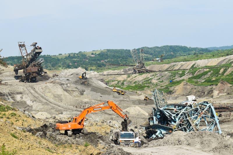 Авария угольной шахты с тяжелой машиной извлечения внутри эксплуатирования угля Огромный экскаватор обрушился в открытом карьере стоковое изображение