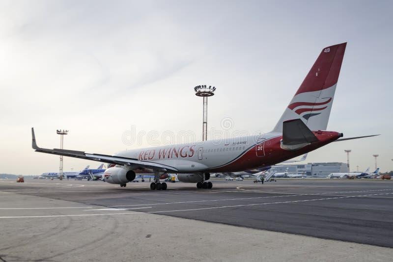 Авиакомпании крылов красного цвета самолета приводятся в действие отбуксировку стоковая фотография rf