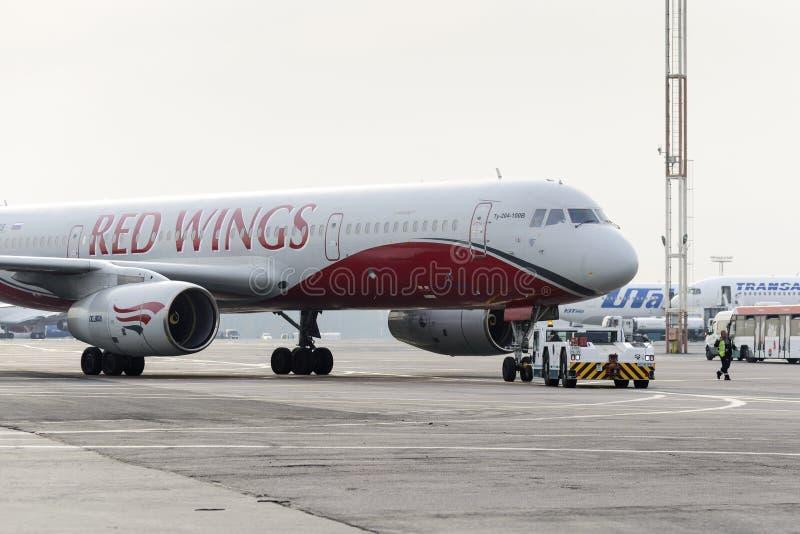 Авиакомпании крылов красного цвета самолета приводятся в действие отбуксировку стоковое изображение