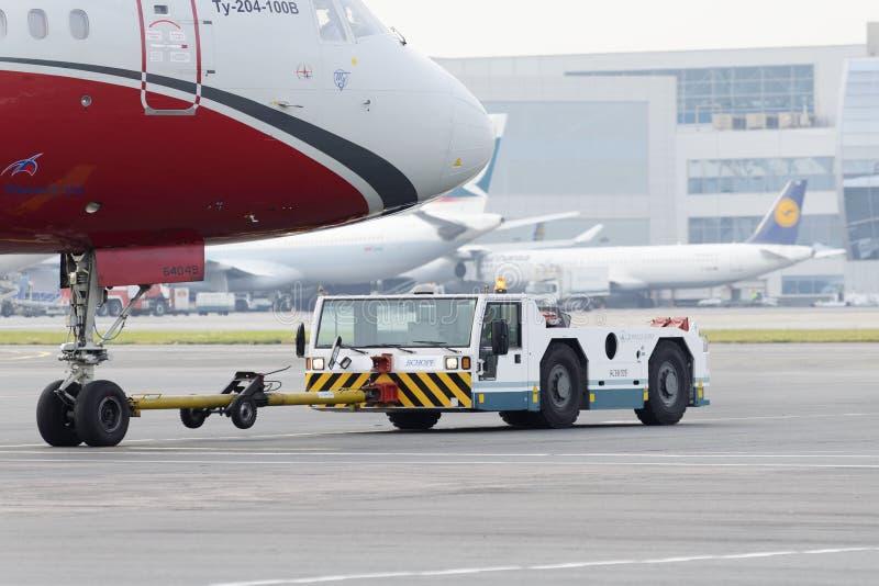 Авиакомпании крылов красного цвета самолета приводятся в действие отбуксировку стоковое изображение rf