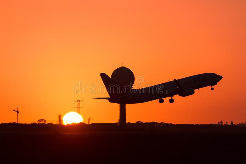 Авиалайнер двигателя принимая на восход солнца стоковое фото