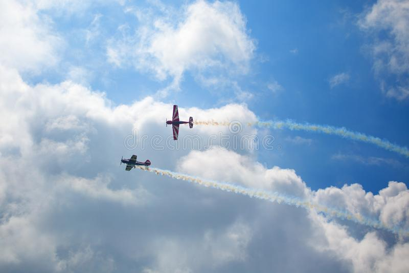 """Авиаполе Mochishche, местный авиасалон, 2 Yak-52, пилотажная команда """"открытое небо """", Barnaul, на голубом небе с предпосылкой об стоковые фото"""