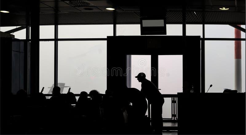 Авиапорт в 0 процентах видимости - силуэтов fogged в пассажирах ждать для того чтобы лететь вне стоковые фотографии rf