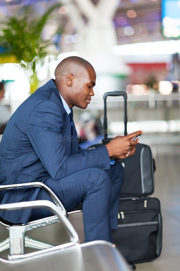 Авиапорт мобильного телефона бизнесмена стоковые изображения rf