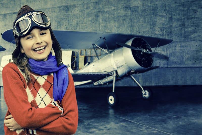 Авиатор, счастливая девушка готовая для того чтобы путешествовать с самолетом. стоковое фото
