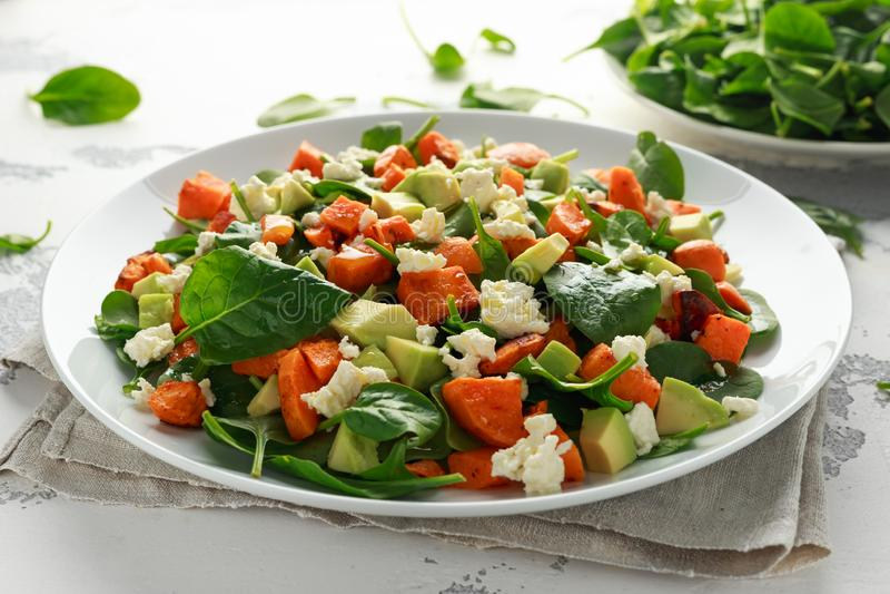 Авокадо, зажаренный в духовке сладкий картофель, шпинат, салат сыра фета здоровый в белой плите стоковые изображения rf