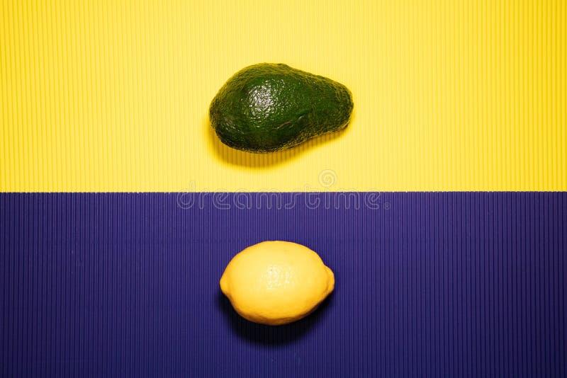 Авокадо и лимон на желтом цвете и пурпурной предпосылке стоковое фото rf