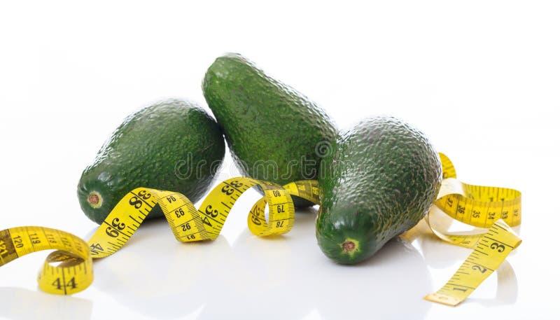 Авокадоы и лента измерения на белой предпосылке стоковое фото rf