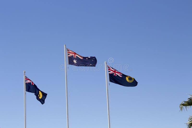 Австралийские и западные австралийские флаги летая против голубого неба стоковое изображение rf