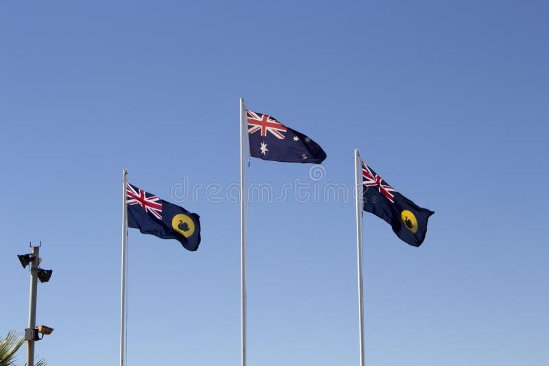 Австралийские и западные австралийские флаги летая против голубого неба стоковое изображение