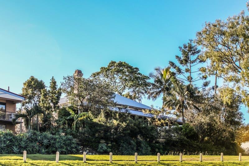 Австралийский дом веранды почти спрятанный в тропической растительно стоковая фотография