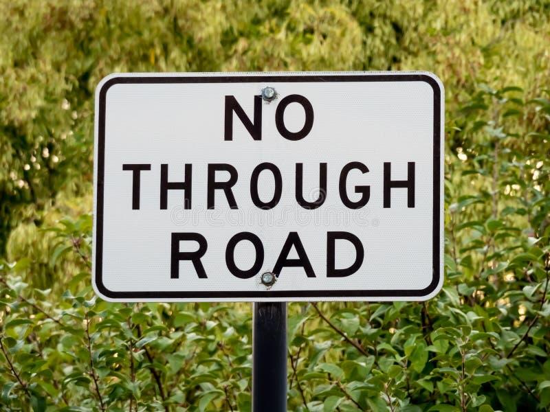 Австралийский дорожный знак НЕ- ЧЕРЕЗ ДОРОГУ перед листьями дерева стоковое фото