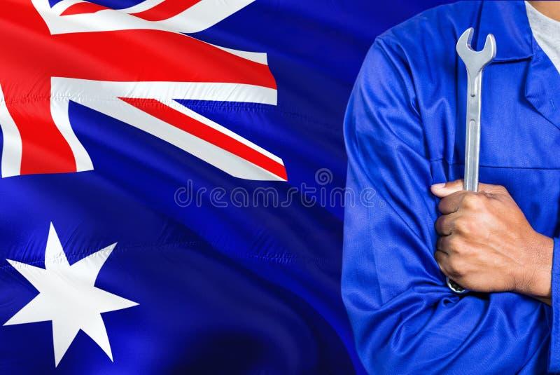 Австралийский механик в голубой форме держит ключ против развевать предпосылка флага Австралии Пересеченный техник оружий стоковое фото