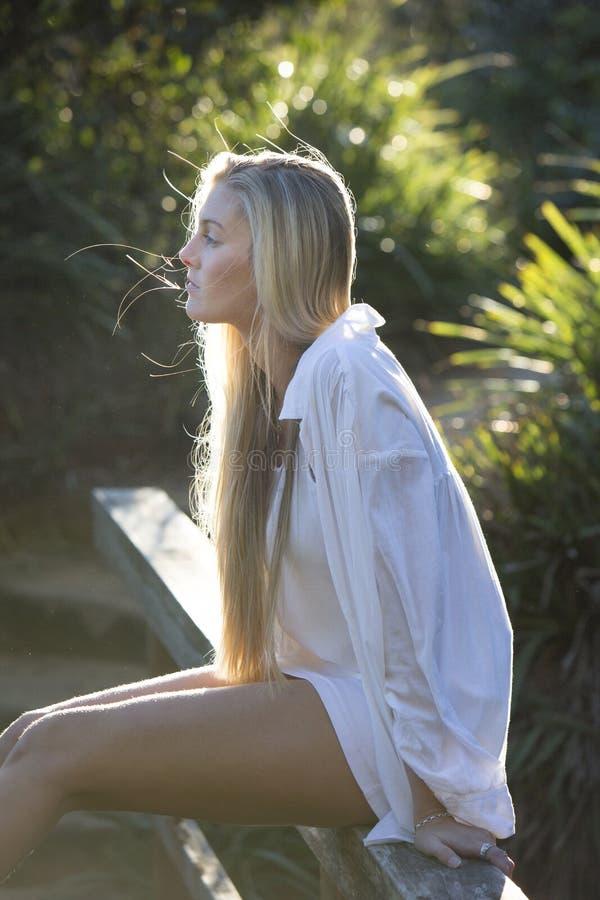 Австралиец при длинные светлые волосы сидя на мосте смотря прочь стоковое изображение rf