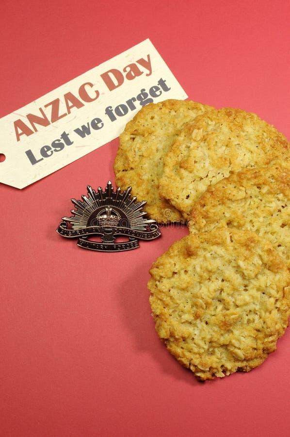 Австралийский значок шлема дня WWI поднимая Солнця ANZAC с традиционными печеньями Anzac и чтобы мы забываем сообщение стоковые изображения rf