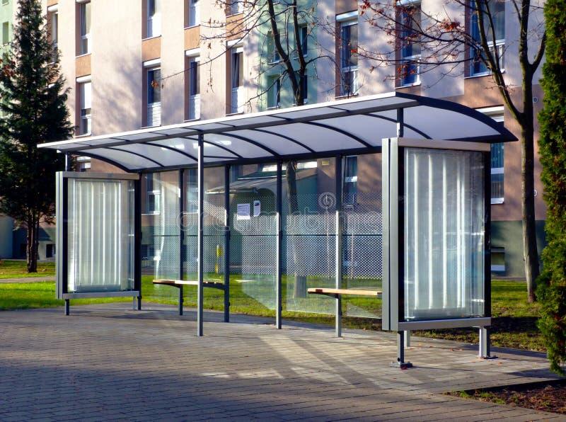 Автобусная остановка на автобусной остановке стеклянной и алюминиевой структуры в парке как устанавливать стоковое изображение