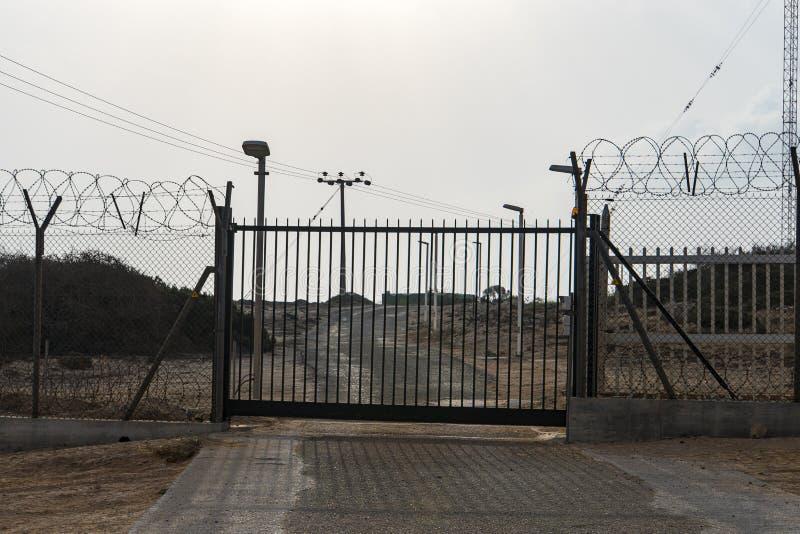 Автоматические ворота металла Блок загородки колючей проволоки путь ворота к закрытой области стоковое фото rf