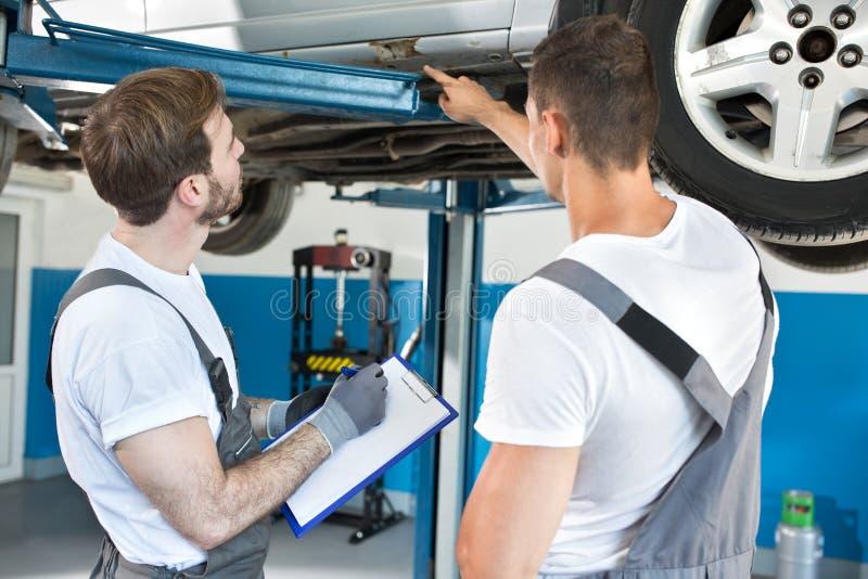 Автоматические механики мастерской проверяя повреждение к автомобилю стоковые фотографии rf