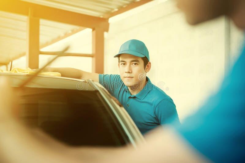 Автоматические обслуживающие персоналы очищая автомобиль стоковые изображения