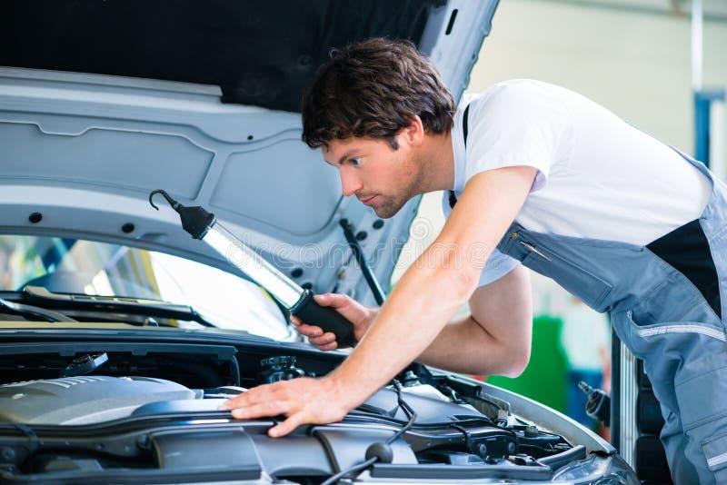 Автоматический механик работая в мастерской обслуживания автомобиля стоковые фотографии rf