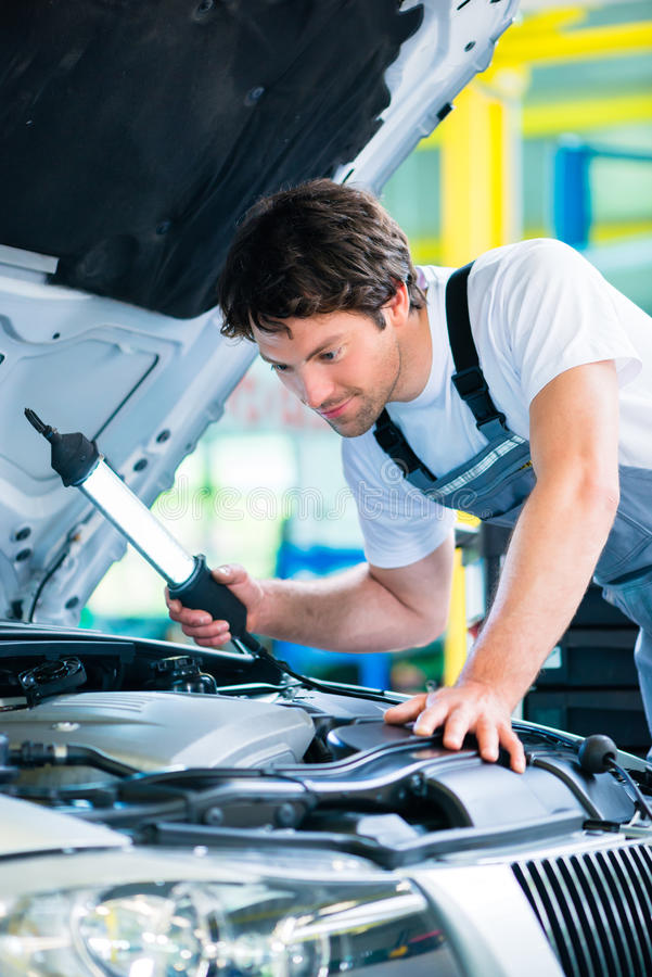 Автоматический механик работая в мастерской обслуживания автомобиля стоковое изображение rf