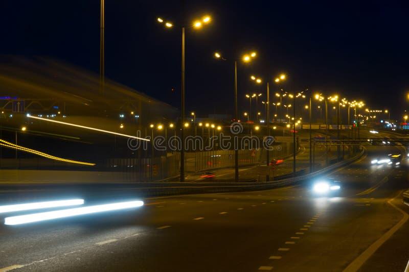 Автомобили движения шоссе на blured ноче Автомобили двигая дальше дорогу на bri стоковые фото