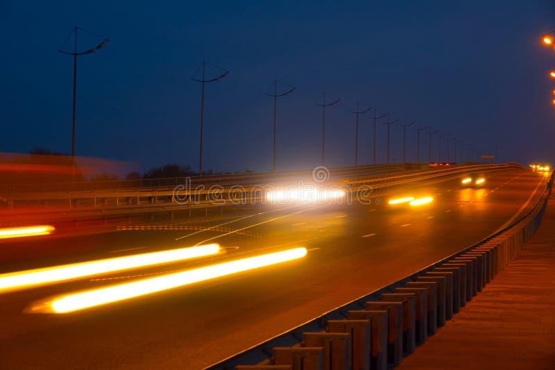 Автомобили движения шоссе на blured ноче Автомобили двигая дальше дорогу на bri стоковая фотография rf