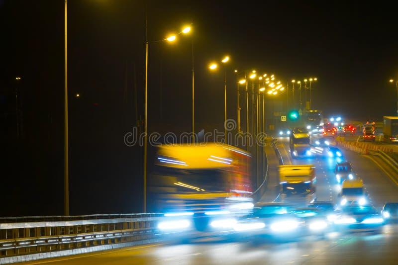 Автомобили движения шоссе на blured ноче Автомобили двигая дальше дорогу на bri стоковое фото rf