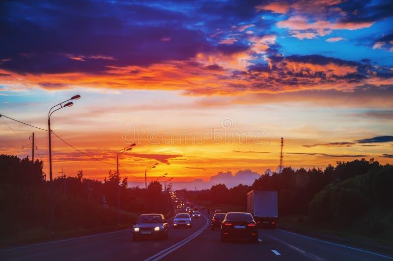 Автомобили едут на заходе солнца на дороге в тумане лета стоковые фотографии rf