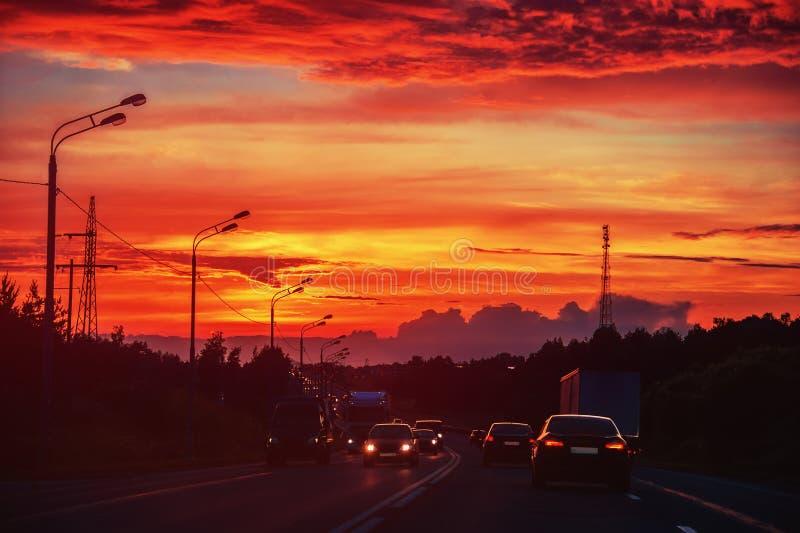 Автомобили едут на заходе солнца на дороге летом стоковые изображения