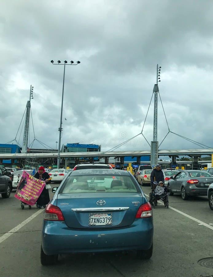 Автомобили ждать в линии для того чтобы пересечь границу от Мексики к США стоковая фотография
