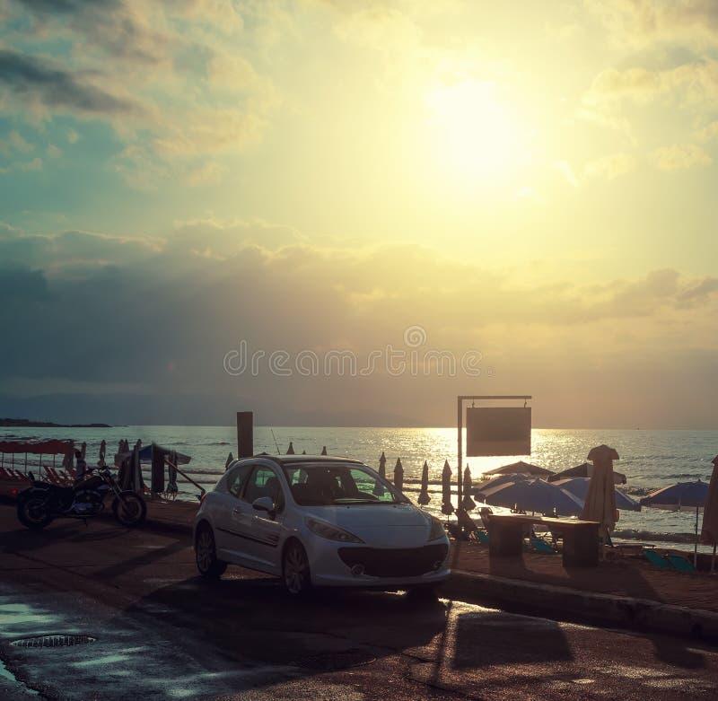 Автомобили и мотоцикл на пляже около пляжа и зонтиков на предпосылке облаков захода солнца и солнца, захода солнца стоковые фото