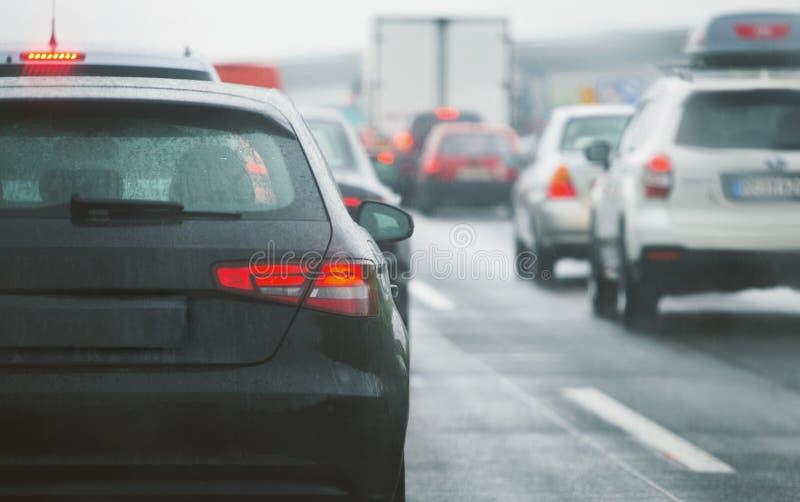Автомобили и тележки затора движения управляя на шоссе дороги стоковая фотография