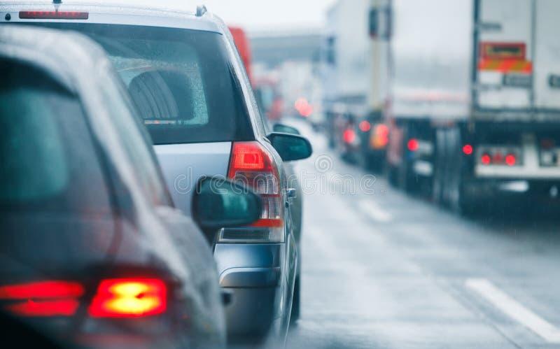 Автомобили и тележки затора движения управляя на шоссе дороги стоковое изображение